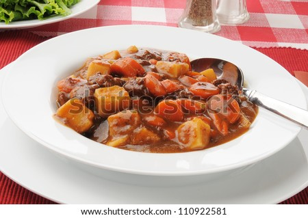 A bowl of beef stew with a green salad