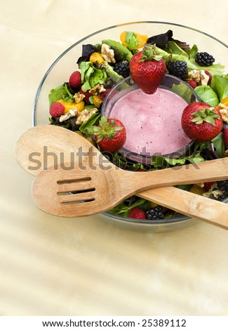A bowl of berry field greens with yogurt dip and wooden serving spoons.