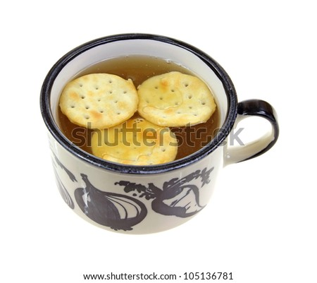 A bowl of canned chicken broth with crackers.