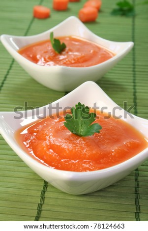 a bowl of carrot soup with fresh parsley - stock photo