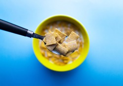 A bowl of cereal in milk. Cereal is made of square pieces, containing a high amount of sugar. The bowl is yellow. Cereal is on it own against a blue background.