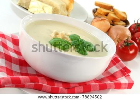 a bowl of cheese soup with croutons and basil