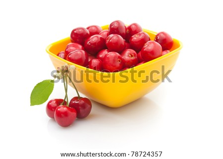 A bowl of cherries with a small group next to it.