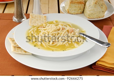 A bowl of chicken noodle soup and soda crackers