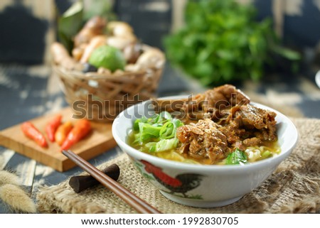 A bowl of chicken noodles with shredded chicken and vegetables.