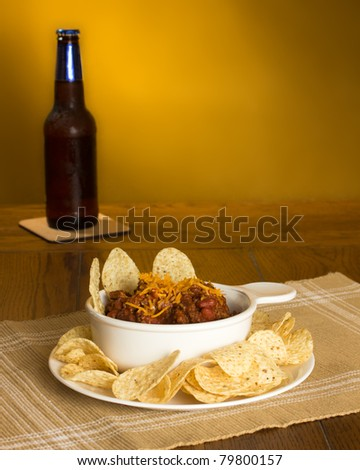 A bowl of chili con carne served with tortilla chips and a bottle of beer