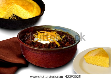 A Bowl of Chili served with Corn Bread on white