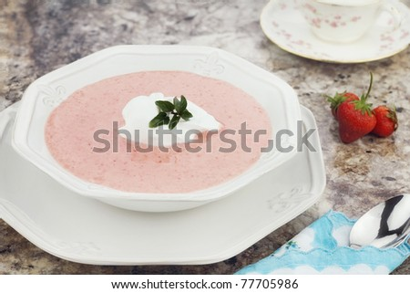 A bowl of chilled strawberry soup, garnished with a dollop of whipped cream and a fresh sprig of chocolate mint.