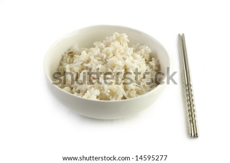 A bowl of cooked brown rice, in an Asian style bowl, with chopsticks isolated on white