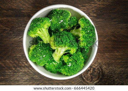 A bowl of cooked green broccoli with sea salt, shot from above on a dark wooden rustic texture with a place for text