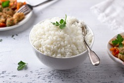 A bowl of cooked rice with a stew of soy meat and vegetables on a light gray background. vegan natural diet food. selective focus, horizontal