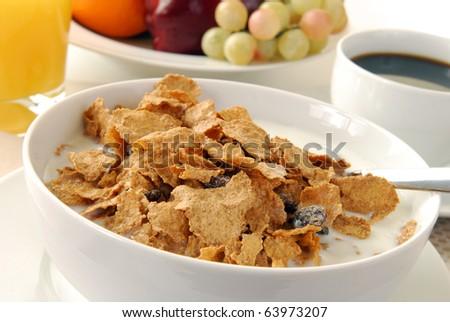 A bowl of corn flakes and raisins - stock photo