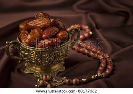 A bowl of dates and an Islamic rosary on velvet background - stock photo