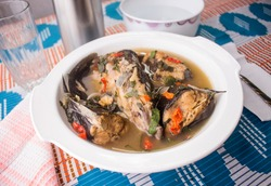 A Bowl of Delicious Catfish Peppersoup Set on a Beautiful Blue and Red Pattern Tablecloth. This is  a Popular Nigerian Local Eat Out Meal.