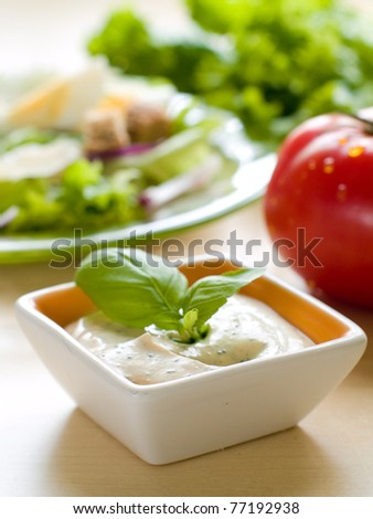 A bowl of dip with salad on background.  Shallow depth of field, selective focus