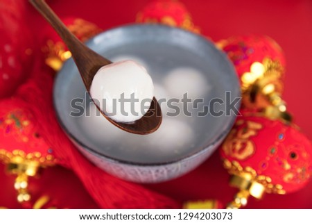 A bowl of dumplings or a bowl of glutinous rice balls and a spoon surrounded by red lanterns on a red background