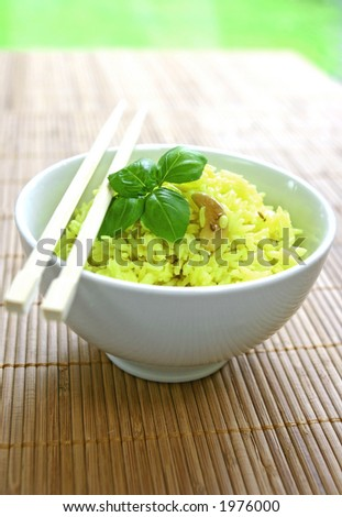 A bowl of fragrant yellow rice with lentils, cumin and cashew nuts garnish with a sprig of basil and a pair of chopsticks on bamboo mat