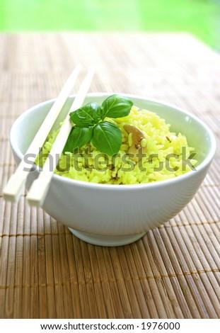 Uma bacia do arroz amarelo perfumado com as porcas dos lentils, docominhos e de caju garnish com um sprig do basil e um par doschopsticks na esteira de bambu