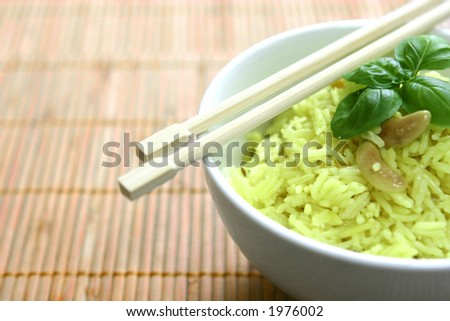 A bowl of fragrant yellow rice with lentils, cumin and cashew nuts garnish with basil leaf and a pair of chopstick on bamboo mat, with copyspace