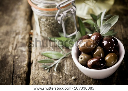 A bowl of fresh black olives and container of dried herbs stand on an old wooden kitchen table for use as ingredients in cooking