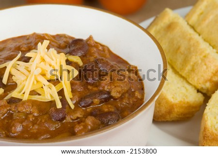 A bowl of fresh, homemade chili, topped with cheese and a nice side of cornbread. Shallow dof.