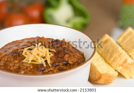 A bowl of fresh, homemade chili, with cornbread on the side and fresh ingredients in the background.