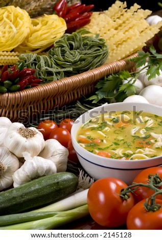 A bowl of fresh soup surrounded by all the ingredients