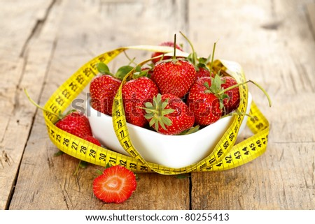 A bowl of fresh strawberries wrapped around with a measure tape