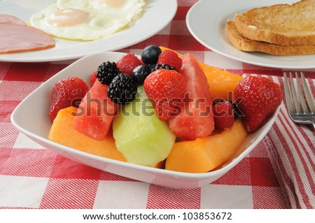 A bowl of fruit salad with melon slices and berries