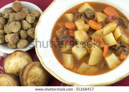 A bowl of homemade beef stew with a side of fresh fried okra and cornbread muffins, horizontal