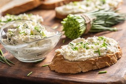 A bowl of homemade cream cheese spread with chopped chives surrounded by bread slices with spread and a bunch of freshly cut chives.
