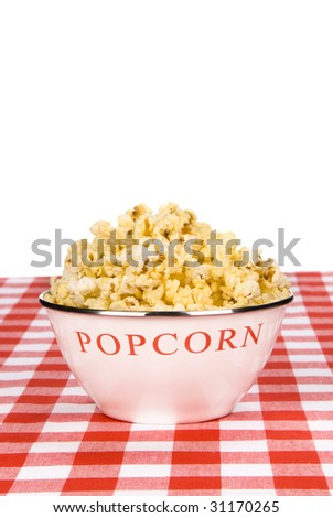 A bowl of hot buttered popcorn on a checkered tablecloth with copy space.
