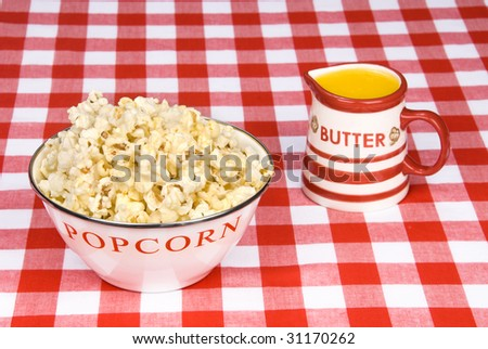 A bowl of hot; freshly popped popcorn and a cup of melted butter on a red and white checkered table cloth.