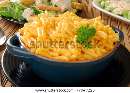 A bowl of hot macaroni and cheese with a chicken and Caesar salad