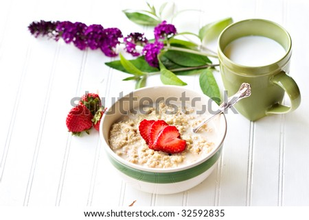 A bowl of hot oatmeal with fresh strawberries cut into the shapes of hearts for a healthy breakfast.