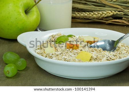 A bowl of muesli with fruit on a wooden table