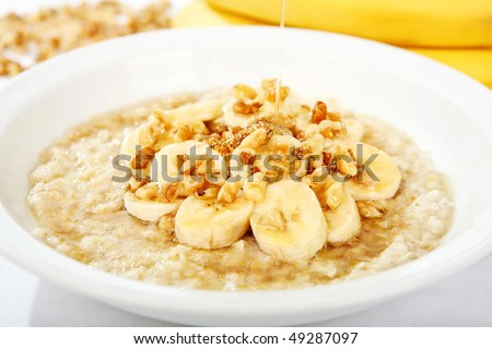 A bowl of oatmeal with bananas and nuts and honey being drizzled over it