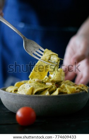 a bowl of pasta with pesto sauce and sliced cherry tomatoes, served on a ceramic mint color plate with a vintage fork all served on a black wooden table #774609433