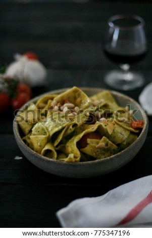 a bowl of pasta with pesto sauce and sliced cherry tomatoes, served on a ceramic mint color plate with a vintage fork all served on a black wooden table with red wine #775347196