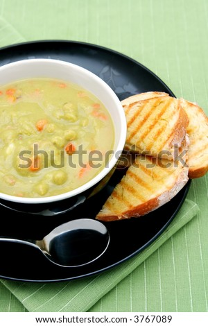 A bowl of pea and ham soup, with fresh toasted sourdough bread. - stock photo