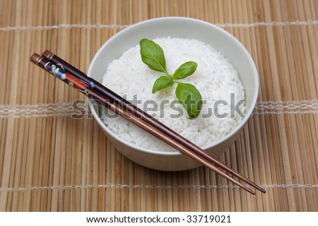 A bowl of perfectly cooked, plain Basmati rice, in an Asian style bowl, with a garnish of Thai Basil