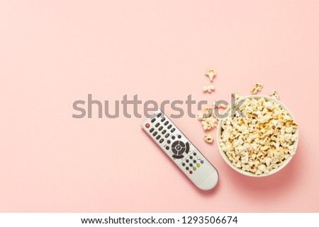 A bowl of popcorn and a TV remote on a pink background. The concept of watching TV, film, TV series, sports, shows. Flat lay, top view.