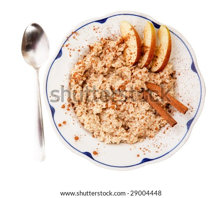 A bowl of porridge with apple and cinnamon spices isolated on white