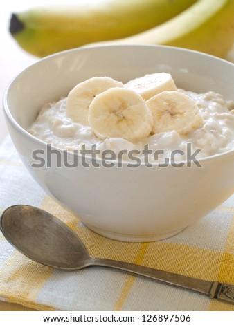 A bowl of porridge with bananas, selective focus