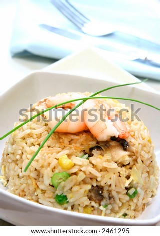 A bowl of prawn, mushroom and egg stir fried rice garnish with chives.