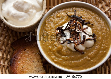 A Bowl of pumpkin curry soup on a wicker  serving dish from top view