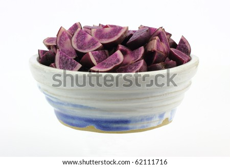 A bowl of quartered purple potatoes prepared for cooking.