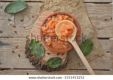 a bowl of quince jam, quince leaves and seeds #1551413252