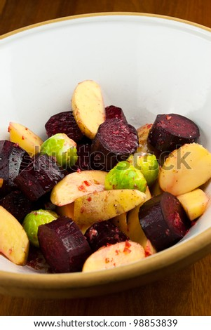 A bowl of raw potatoes, beetroots and brussels sprouts