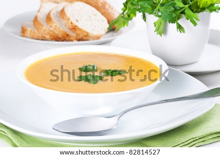 A bowl of soup and few slices of bread - stock photo